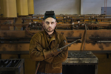 Portrait of Hispanic welder holding torch