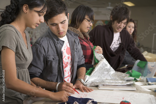 Fashion design students working on sketches in classroom