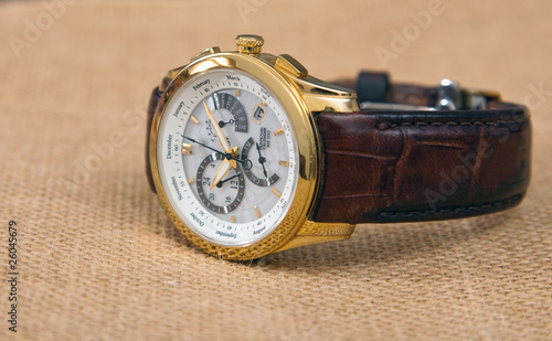 Contemporary men's wrist watch isolated on light color fabric