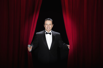 Hispanic man in tuxedo emerging from red curtains