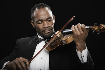 African American man in tuxedo playing violin