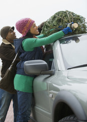 Couple fastening Christmas tree on top of car