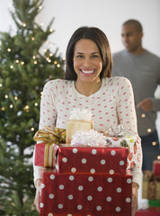 Mixed race woman holding Christmas gifts by tree