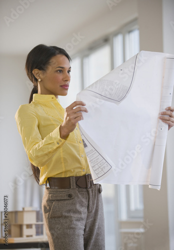 Mixed race architect examining blueprint