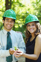 Hispanic business people with green hard hats holding tree sprout