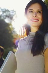 Hispanic woman holding laptop