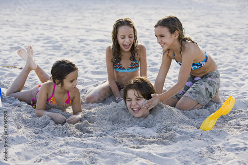 Hispanic girls burying Hispanic boy in sand