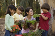 Hispanic woman and children holding potted plants