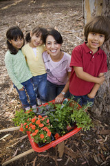 Hispanic woman and children with potted plants and flowers