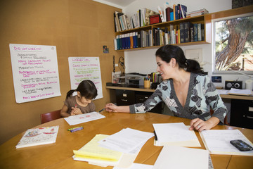 Hispanic mother and daughter in home office