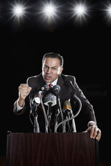 Hispanic man at press conference podium gesturing angrily