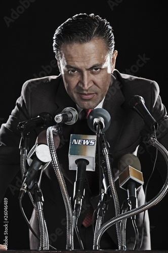 Hispanic man standing at press conference microphones
