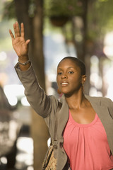 African businesswoman hailing taxi