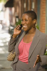 African businesswoman talking on cell phone outdoors
