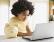 Mixed race girl using laptop next to piggy bank