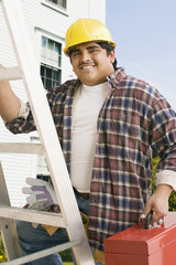 Hispanic man in hard hat climbing ladder with tool box