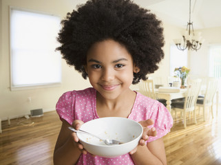 Mixed race girl holding empty cereal bowl