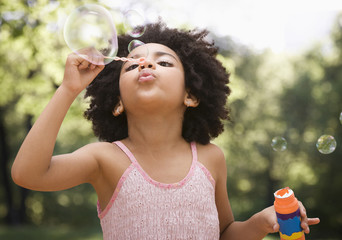 Mixed race girl blowing bubbles