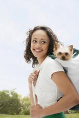 Mixed race teenage girl carrying dog on back