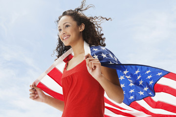 Mixed race teenage girl wrapped in American flag