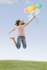 Mixed race teenage girl jumping and holding balloons