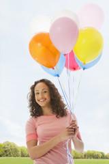 Mixed race teenage girl holding bunch of balloons