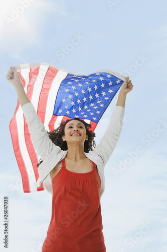 Mixed race teenage girl raising American flag