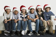 Teenage friends in santa hats sitting on sofa