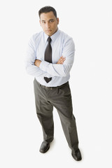 Serious Hispanic businessman standing with arms crossed