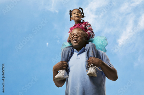 African father carrying daughter on shoulders while daughter covers his eyes