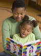 African girl reading ABC book to mother