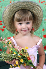 girl in a straw hat with a bouquet of wildflowers