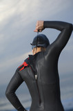 Hispanic woman zipping wetsuit on beach
