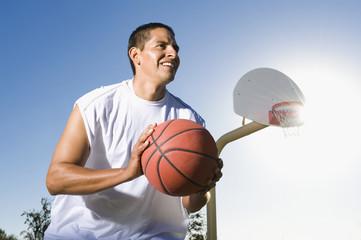 Man playing basketball outdoors