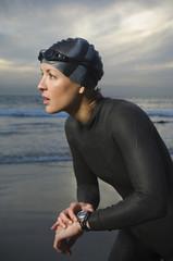 Hispanic woman in wetsuit on beach