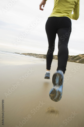 Hispanic woman running on beach