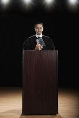 Hispanic priest standing at podium