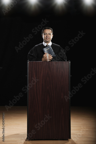 Hispanic priest standing at podium