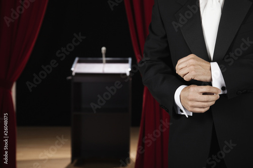 Hispanic man adjusting cuffs near podium