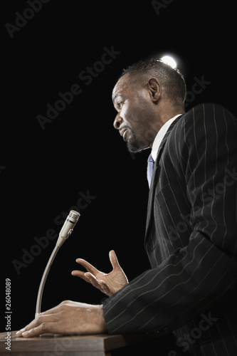 African businessman speaking at podium