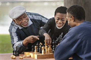 African boy playing chess against father outdoors