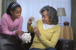 African woman giving granddaughter dollar bill for piggy bank