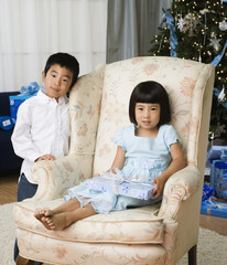 Asian brother and sister in living room with Christmas gift