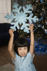 Asian girl in living room with large Christmas snowflake