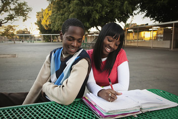 African teenage couple sitting in school yard