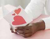 African woman holding ValentineÕs Day card