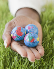 African woman holding three small globes in grass