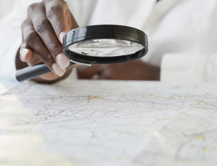 African woman using magnifying glass on map
