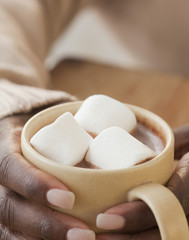 African woman holding cup of hot chocolate and marshmallows