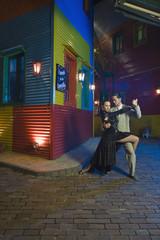 Hispanic couple performing tango on city street